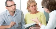 Older couple with pamphlets in hand listening intently to a professional explain something.