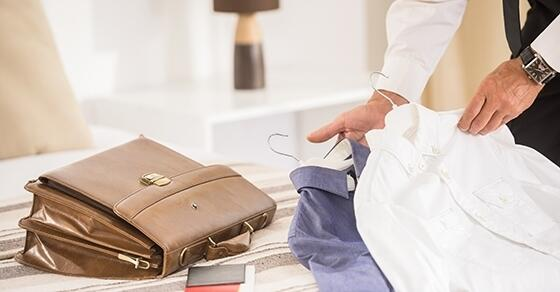 Business professional folding dress shirts next to briefcase.
