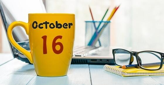 "Yellow coffee mug decorated with ""October 16"" on a desk."