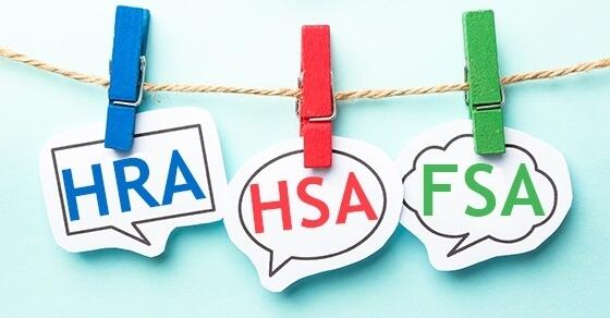 "Cutouts of ""HRA"", ""HSA"", and ""FSA"" hanging on a line with clips."