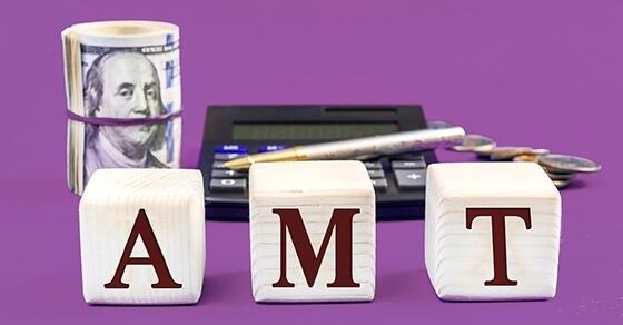 "Wooden blocks that spell out ""AMT"" in front of a roll of money and a calculator."