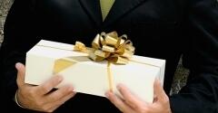 Person holding a present wrapped in white with a gold ribbon.