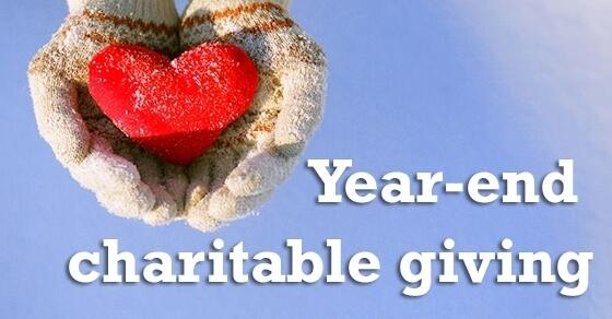 "Gloved hands holding a red heart, ""Year-end charitable giving"""