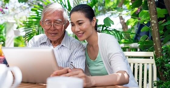 Woman and her elderly parent looking at a device together