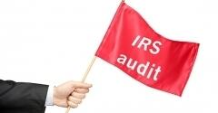 Businessman holding red IRS audit flag