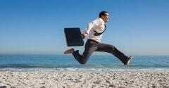 Businessman with briefcase leaping on a beach