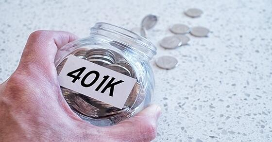 Person holding a jar of 401K coins