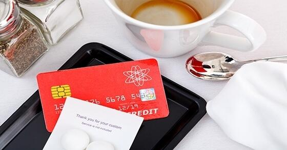 Credit card next to empty coffee cup at restaurant
