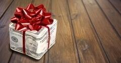 Present wrapped with money and a red bow sitting on a wooden surface.