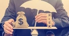Man Holding Umbrella Balancing a Bag of Money with Scrabble Letters Spelling Out