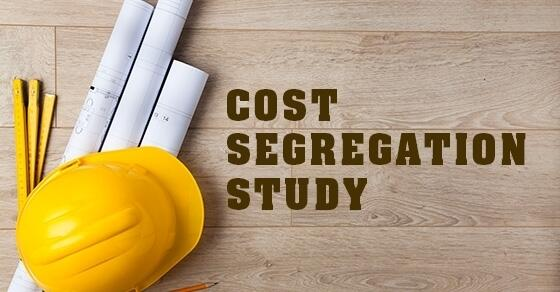 "Hardhat and blueprint on a table with words ""Cost Segregation Study"" next to them."