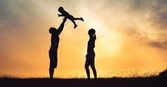 Silhouette of family standing on a hill, child being thrown up into the air by father.