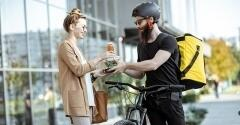 Delivery man on bike handing food and drink over to woman.